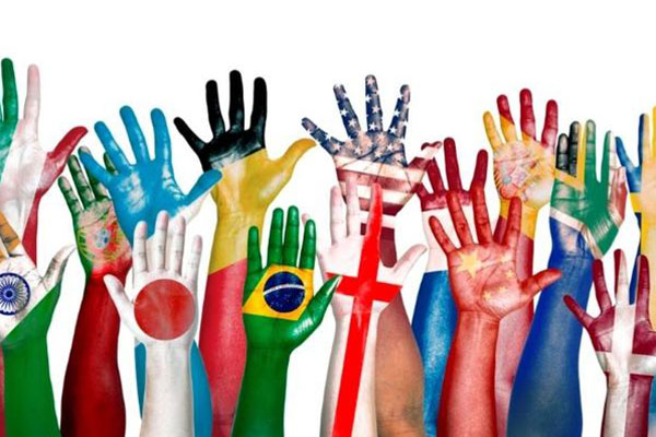 raised hands painted with the colors of different international flags